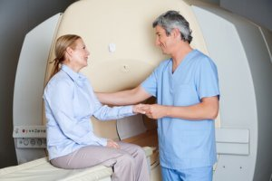 Male radiologic technician comforting female patient before MRI scan